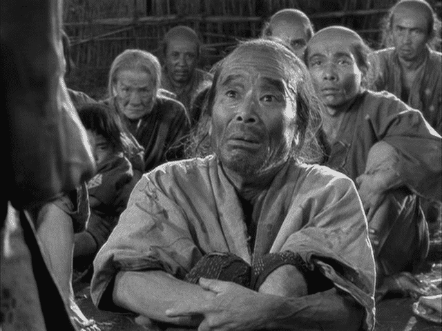 Paysans japonais regardant le héros les bras croisés